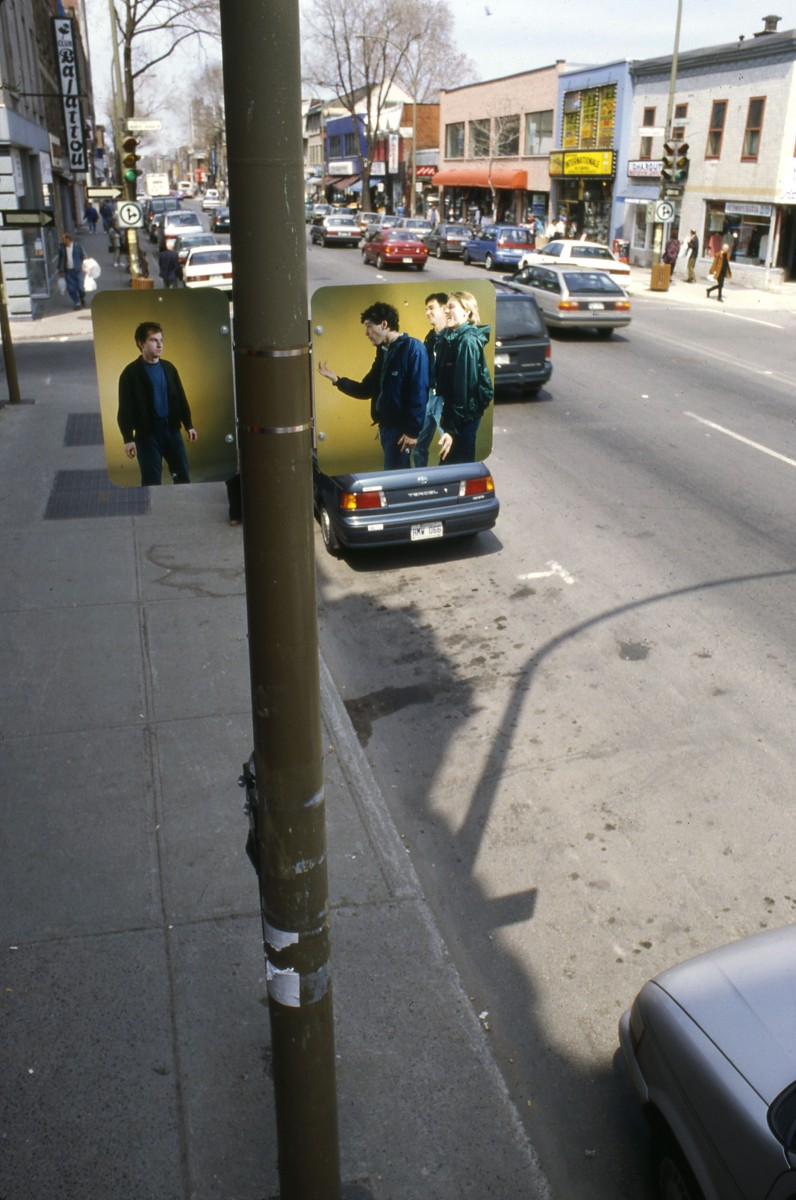 """Hésitation"" from <i></i>, 1996 –  										 – Installation view of three-part grouping 'Gang vs Individual' on opposite side of street from single image, lamp posts on boul. Saint-Laurent"